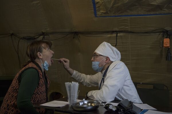 Врач проводит прием пациента на базе госпиталя развернутого Министерством обороны России на территории аэропорта в Степанакерте - Sputnik Таджикистан