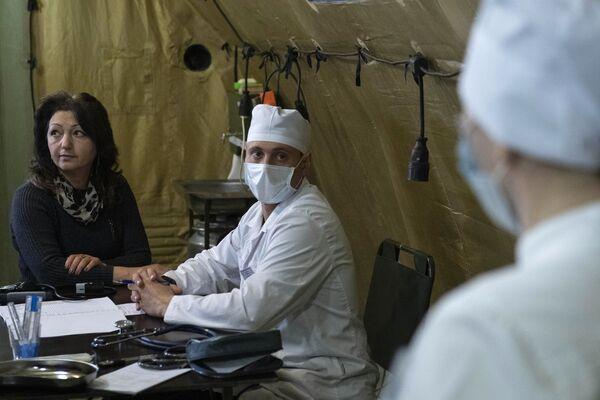 Врач проводит прием пациента на базе полевого госпиталя развернутого Министерством обороны России на территории аэропорта в Степанакерте - Sputnik Таджикистан