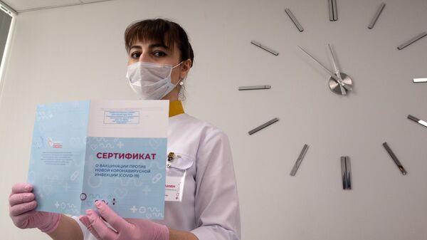 Медработник демонстрирует Сертификат о вакцинации от новой коронавируссной инфекции COVID-19 в Москве - Sputnik Таджикистан