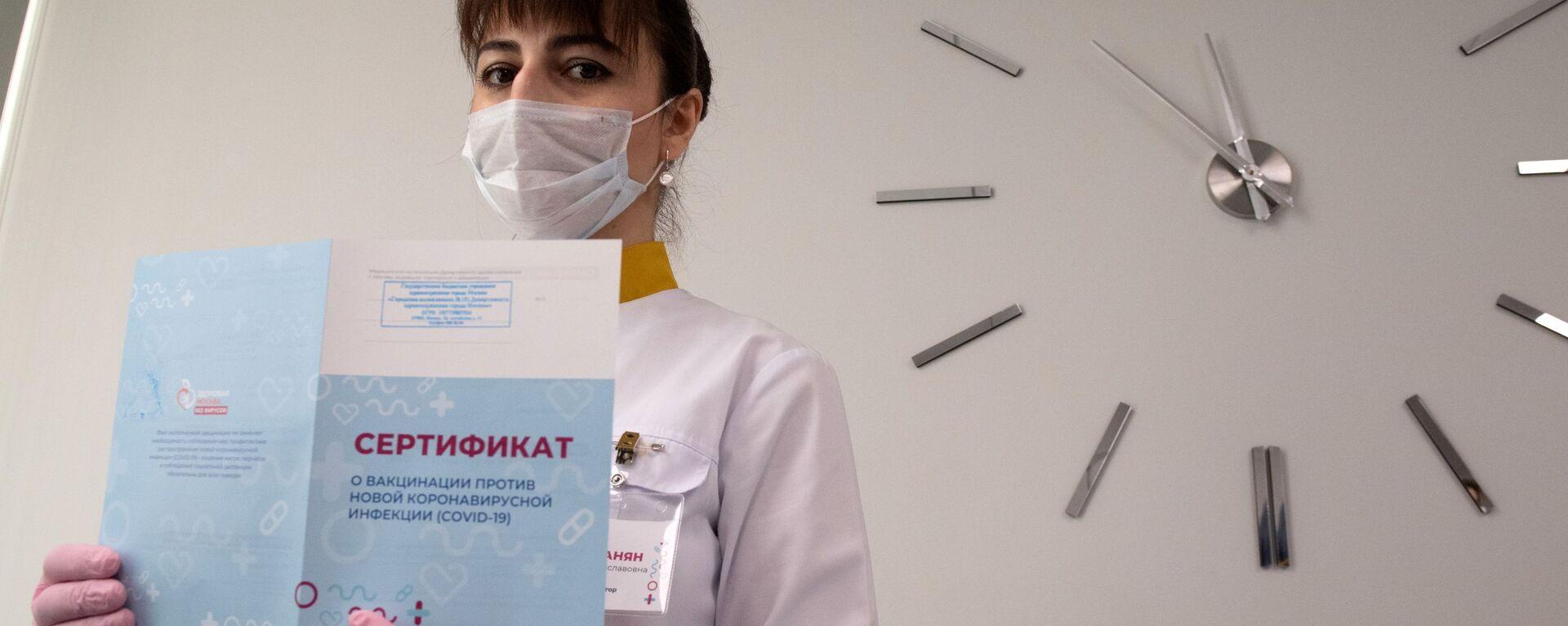 Медработник демонстрирует Сертификат о вакцинации от новой коронавируссной инфекции COVID-19 в Москве - Sputnik Таджикистан, 1920, 16.07.2021