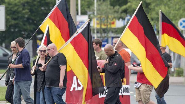 Люди проводят демонстрацию с немецкими флагами в Германии - Sputnik Таджикистан