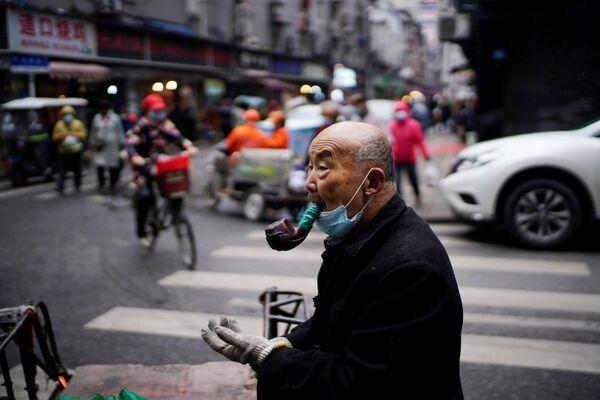 Пожилой мужчина курит трубку на уличном рынке в Ухане - Sputnik Таджикистан