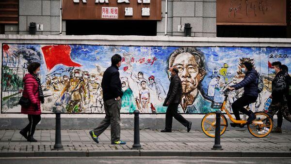 Люди в масках напротив граффити в Ухане почти год после начала пандемии  - Sputnik Тоҷикистон