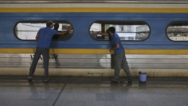 Двое рабочих моют окна у вагоне поезда на центральном вокзале Тегерана - Sputnik Тоҷикистон