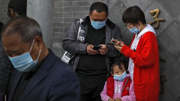 Люди в масках в Пекине, просматривают свои телефоны - Sputnik Таджикистан