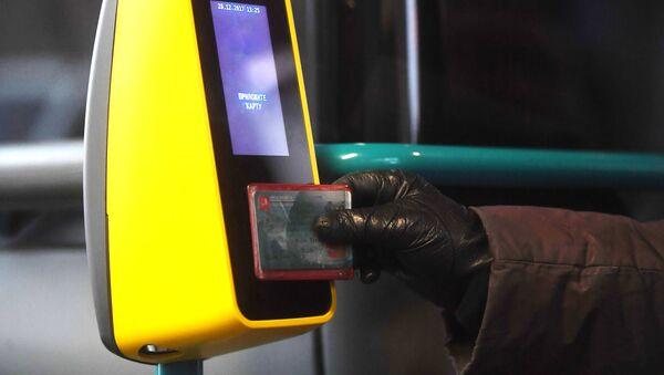 Пассажир прикладывает билет к валидатору в автобусе, архивное фото - Sputnik Таджикистан