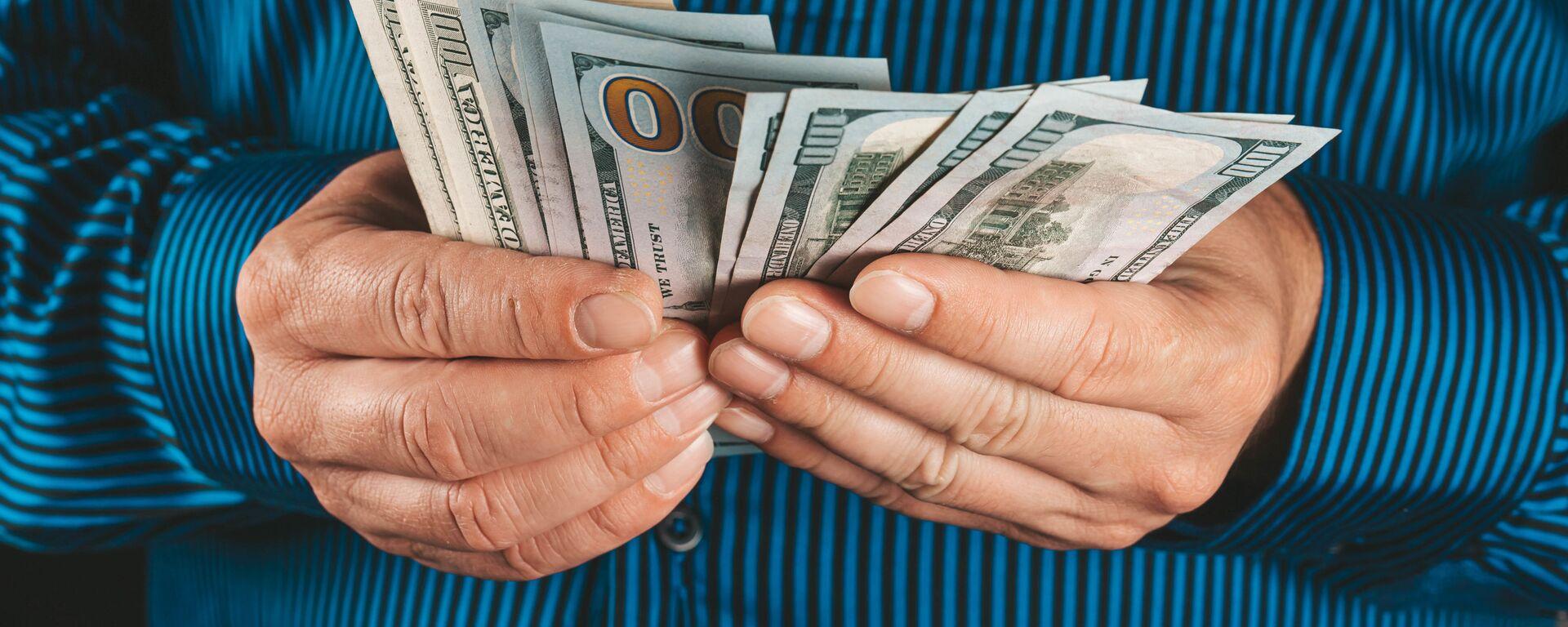 Доллары в руках - Sputnik Таджикистан, 1920, 23.12.2020