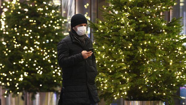Человек идет по улице вдоль новогодних елок - Sputnik Таджикистан