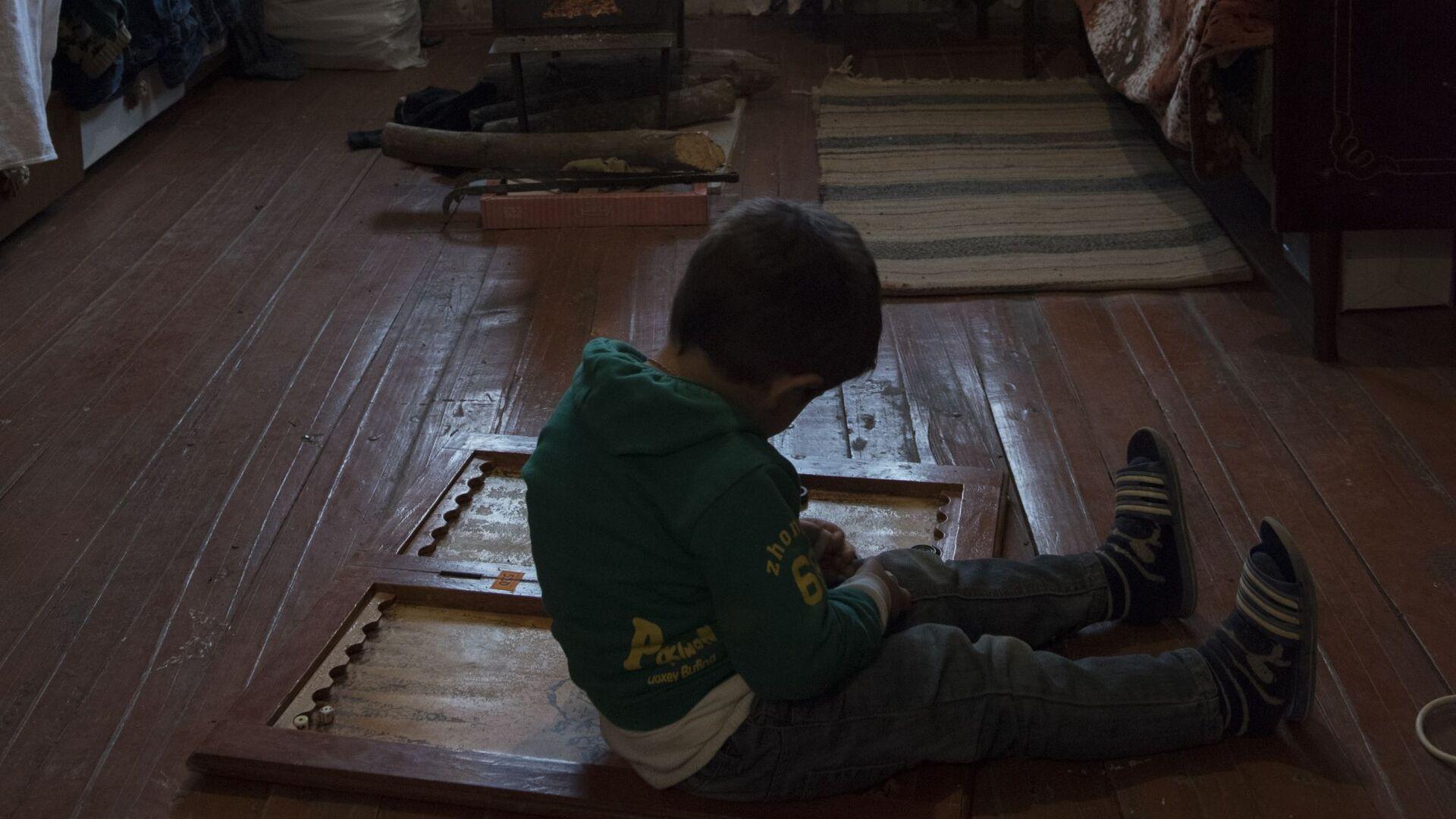 Мальчик сидит на полу в комнате в доме города Мартакерт в Нагорном Карабахе - Sputnik Тоҷикистон, 1920, 12.08.2021