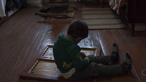 Мальчик сидит на полу в комнате в доме города Мартакерт в Нагорном Карабахе - Sputnik Тоҷикистон