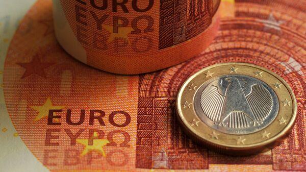 Монета номиналом 1 евро на фоне фрагмента банкноты номиналом 10 евро.  - Sputnik Таджикистан