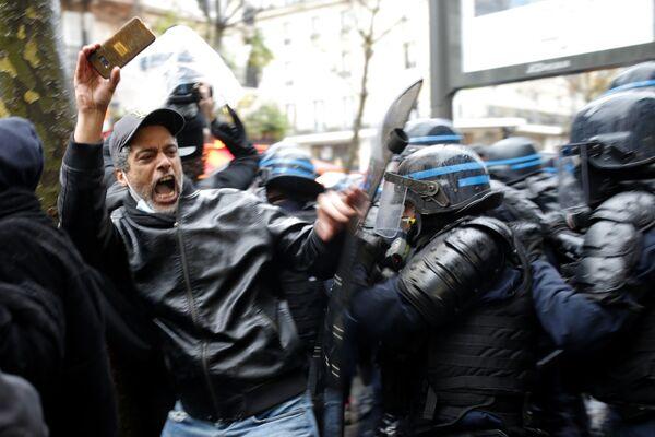 Участник протеста и полицейские в Париже  - Sputnik Таджикистан