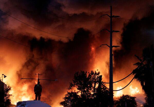 Пожарник стоит на резервуаре с водой во время пожара на заводе по переработке металлолома компании Deacero в Гуадалупе, на окраине Монтеррея, Мексика - Sputnik Таджикистан