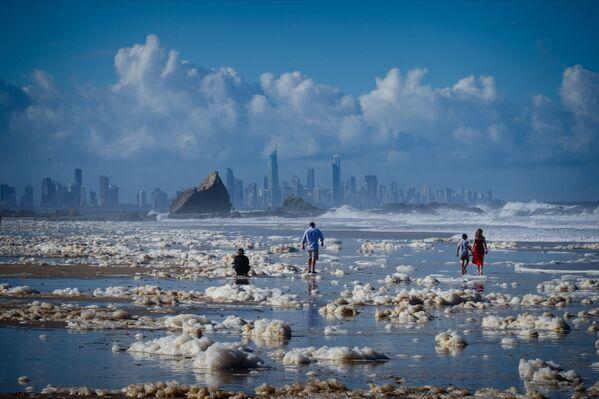 Туристы гуляют среди пены на пляже после циклона в Австралии - Sputnik Таджикистан