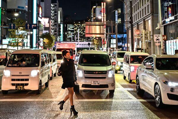 Женщина в защитной маске переходит дорогу в Токио - Sputnik Таджикистан