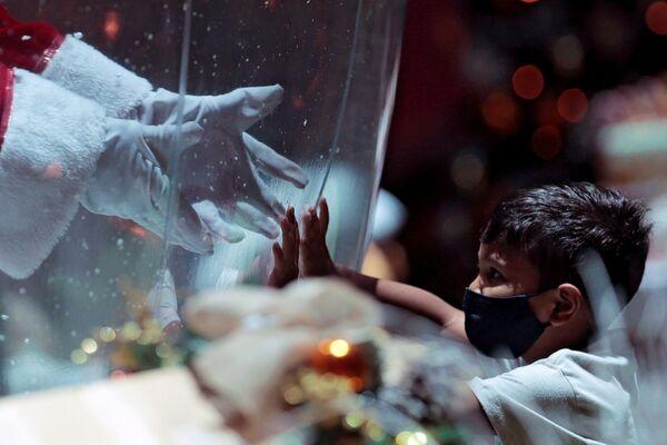 Ребенок общается с Санта Клаусом через пластиковый экран в шоппинг-центре в Бразилии - Sputnik Таджикистан