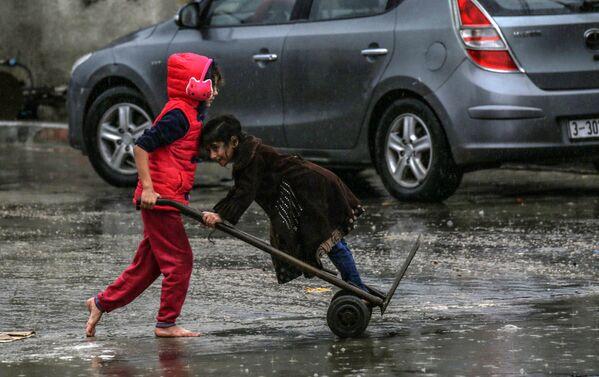 Палестинские дети в дождливый день в Рафахе - на юге сектора Газа - Sputnik Таджикистан