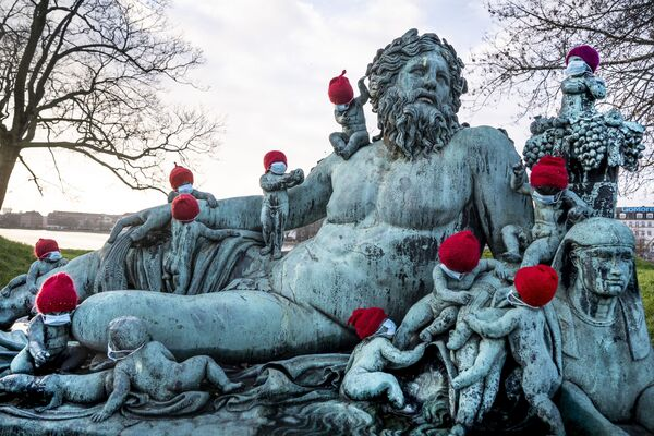 Маленькие бронзовые статуи в рождественских колпаках и масках в Копенгагене  - Sputnik Таджикистан