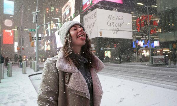 Турист во время снегопада на Таймс-сквер в Нью-Йорке - Sputnik Таджикистан
