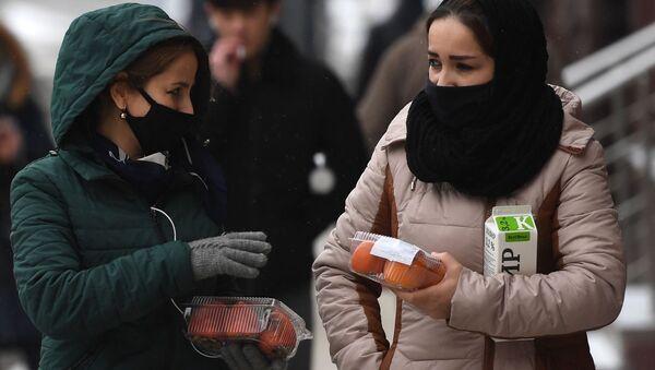 Девушки в защитных масках на одной из улиц в Москве - Sputnik Таджикистан