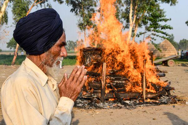 Отец на церемонии кремации своего сына, погибшего в результате пограничного конфликта Индии и Китая - Sputnik Таджикистан