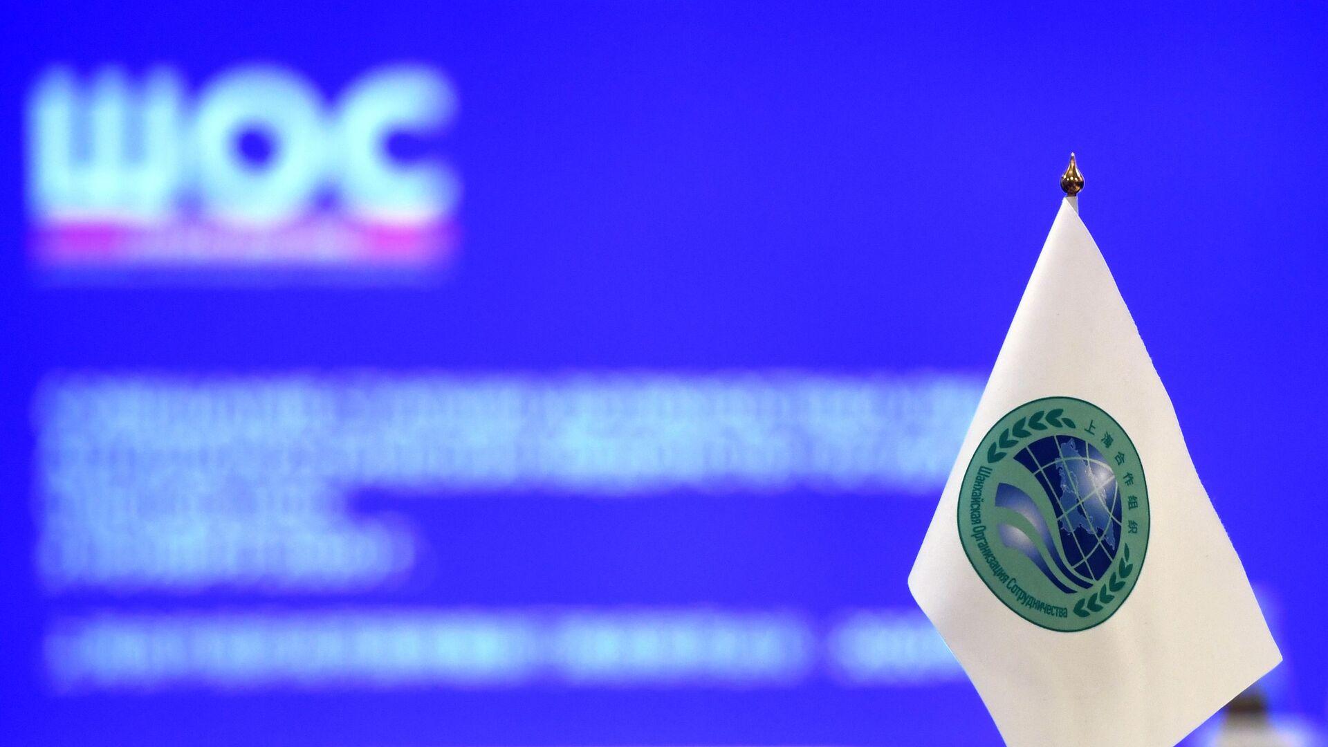 Флажок с логотипом Шанхайской организации сотрудничества (ШОС) - Sputnik Тоҷикистон, 1920, 09.09.2021