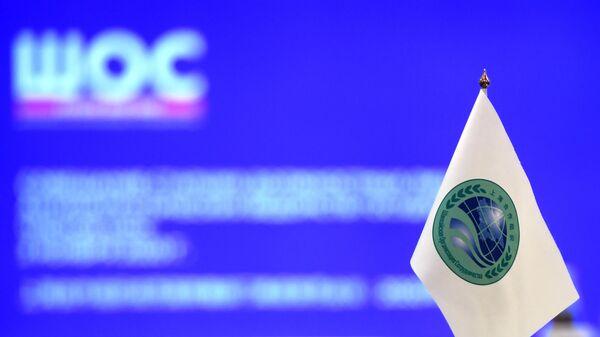 Флажок с логотипом Шанхайской организации сотрудничества (ШОС) - Sputnik Тоҷикистон