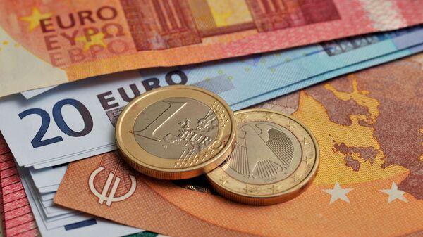 Монеты номиналом 1 евро на фоне банкнот номиналом 10 и 20 евро.  - Sputnik Тоҷикистон