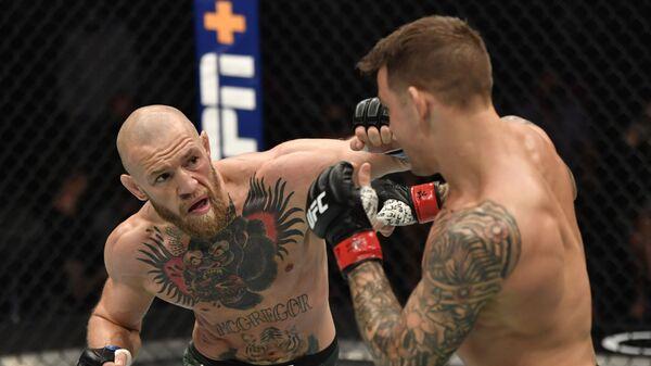 Конор МакГрегор из Ирландии наносит удар Дастину Порье в бою в легком весе во время события UFC 257 - Sputnik Таджикистан
