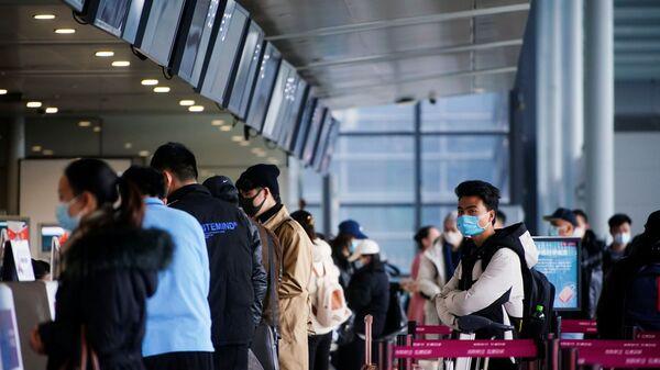 Путешественники в защитных масках в очереди в Шанхайском аэропорте, Китай - Sputnik Таджикистан