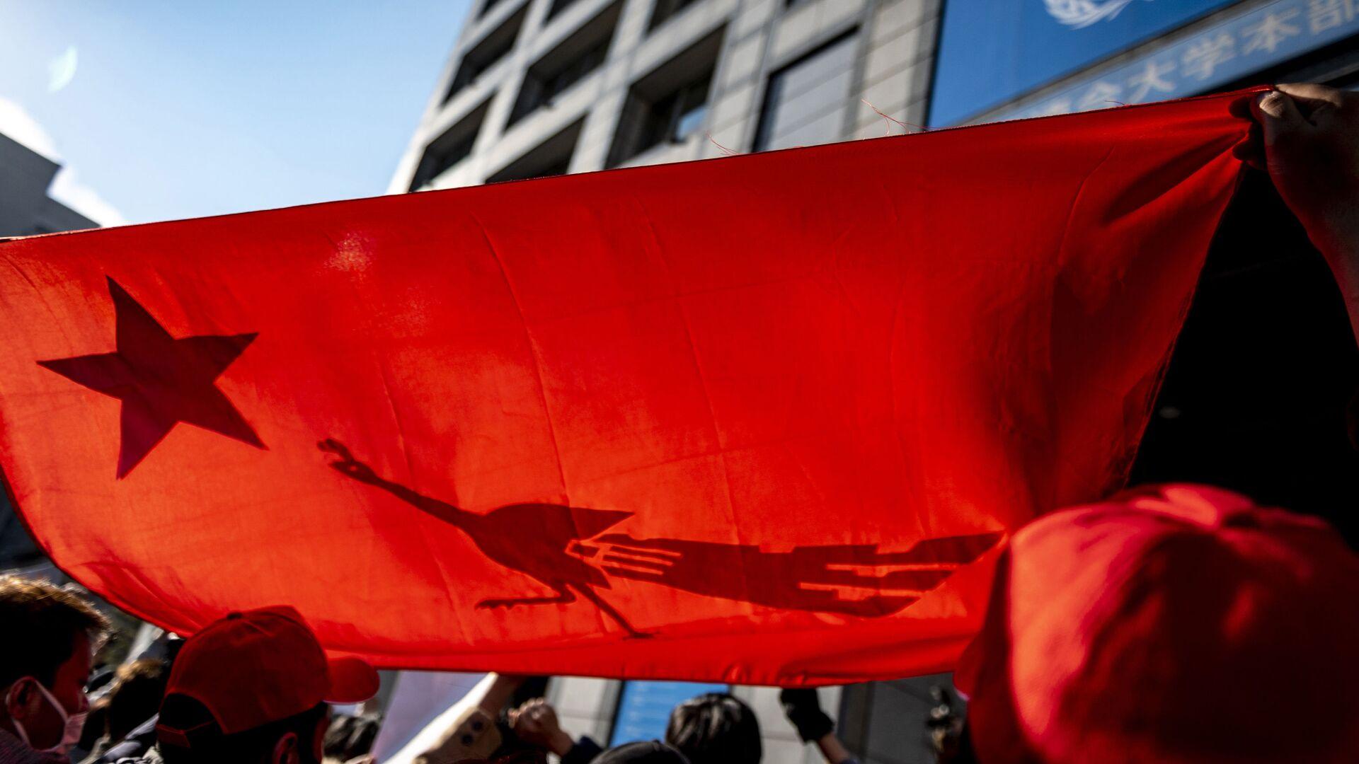 Активисты Мьянмы скандируют лозунги и держат флаг Национальной лиги за демократию во время акции протеста - Sputnik Таджикистан, 1920, 08.04.2021