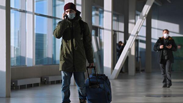 Пассажир в защитной маске в международном аэропорту  - Sputnik Таджикистан