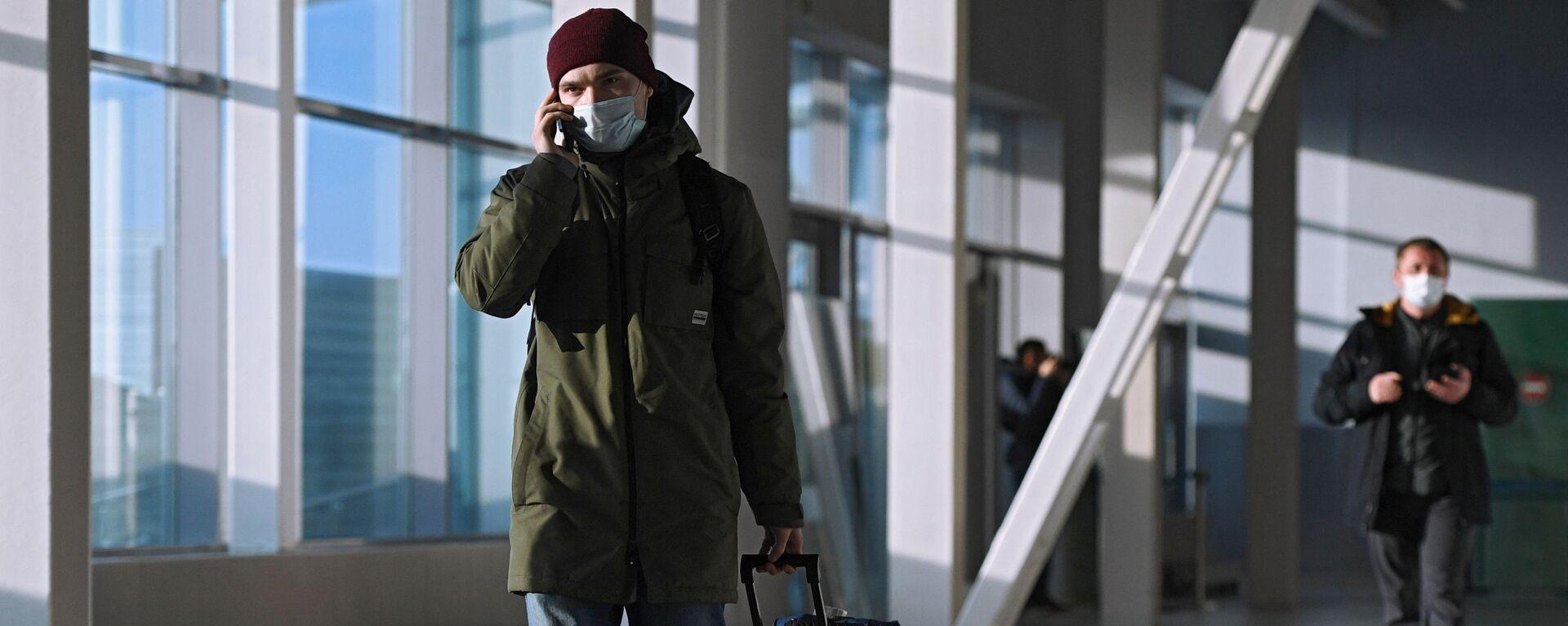 Пассажир в защитной маске в международном аэропорту  - Sputnik Таджикистан, 1920, 24.09.2021