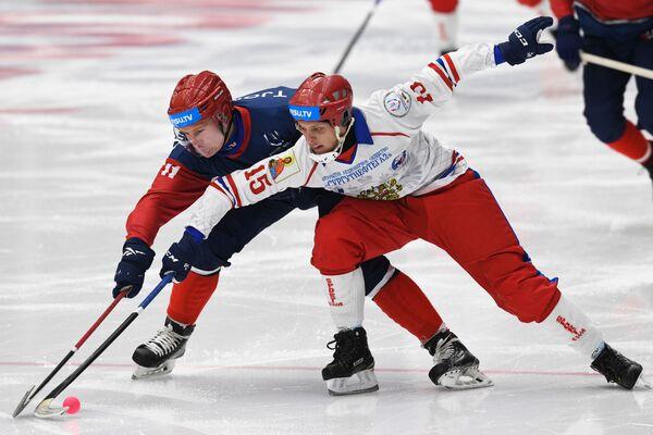 Слева направо: Йонас Тъемстад  (Норвегия) и Михаил Сергеев (Россия) в матче группового этапа соревнований по хоккею с мячом среди мужчин - Sputnik Таджикистан