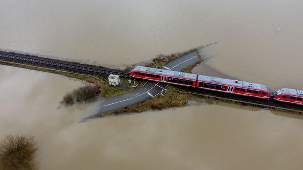 Поезд проезжает по железной дороге на затопленной местности в Германии  - Sputnik Таджикистан