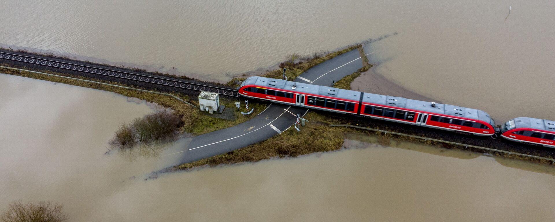 Поезд проезжает по железной дороге на затопленной местности в Германии  - Sputnik Таджикистан, 1920, 30.06.2021