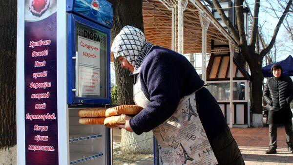 Женщина с лепешками в Худжанде возле ящика добра - Sputnik Тоҷикистон