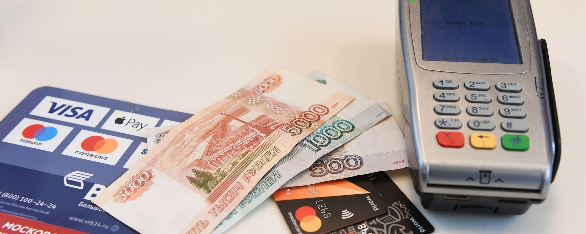 Терминал оплаты банковскими картами и денежные купюры - Sputnik Таджикистан, 1920, 18.06.2021