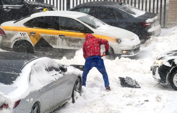 Мужчина откапывает из сугроба свою машину во дворе жилого дома в Москве - Sputnik Таджикистан