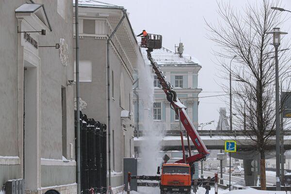 Работник коммунальной службы убирает снег с крыши здания Музея Москвы на Зубовском бульваре в Москве. - Sputnik Таджикистан