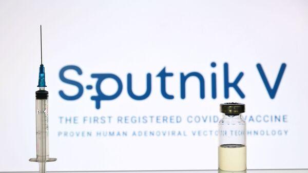 Шприц и ампула на фоне логотипа Спутник V - Sputnik Тоҷикистон