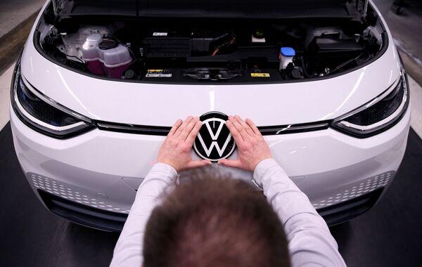 Рабочий устанавливает логотип VW на электромобиле Volkswagen ID.3 на сборочном конвейере автозавода Volkswagen - Sputnik Таджикистан