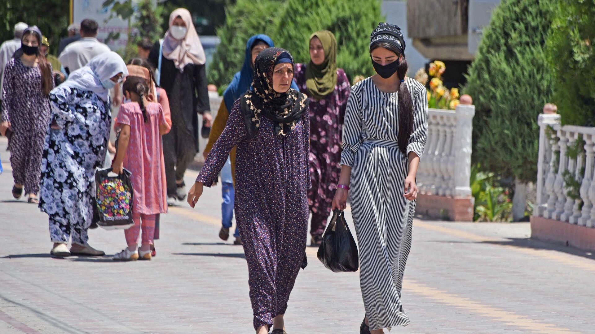 Девушки идут по улице в защитных масках - Sputnik Таджикистан, 1920, 17.07.2021