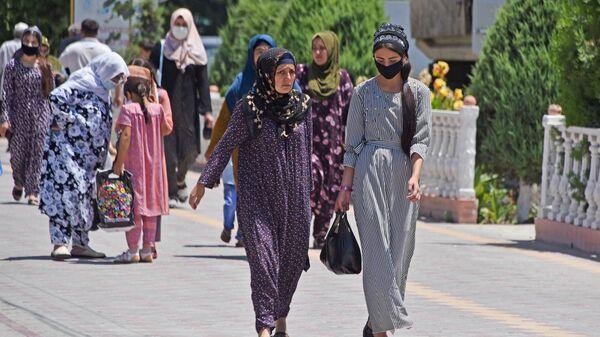 Девушки идут по улице в защитных масках - Sputnik Таджикистан