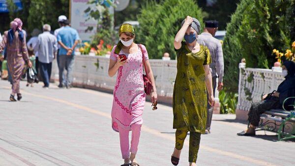 Девушки идут по улице в защитных масках - Sputnik Тоҷикистон