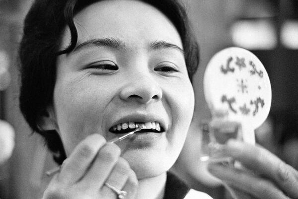 Женские зубы в Японии в разное время выделялись цветом. В древности женщины покрывали зубы черным лаком в знак красоты. Позже это стало обычаем только для замужних женщин. Тошико Фукаям наносит цветное покрытие на свои зубы, 7 апреля 1966 года, Япония - Sputnik Таджикистан