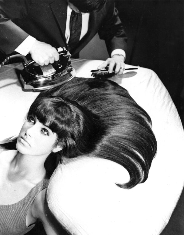 Прообраз современных утюжков для волос. Парикмахер расчесывает и гладит волосы модели на доске, предназначенной для глажки волос. Доска конструирована так, чтобы соответствовать контуру головы и позволять волосам распускаться веером. 20 октября 1965 года, Нью-Йорк - Sputnik Таджикистан