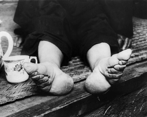 Национальное правительство в Нанкине сейчас пытается искоренить связанные ноги, которые в течение многих лет причиняли страдания женщинам и детям. Китайские женщины пытаются сделать ноги меньше, связывая их в детстве. Фото сделано от 21 сентября 1936 года - Sputnik Таджикистан