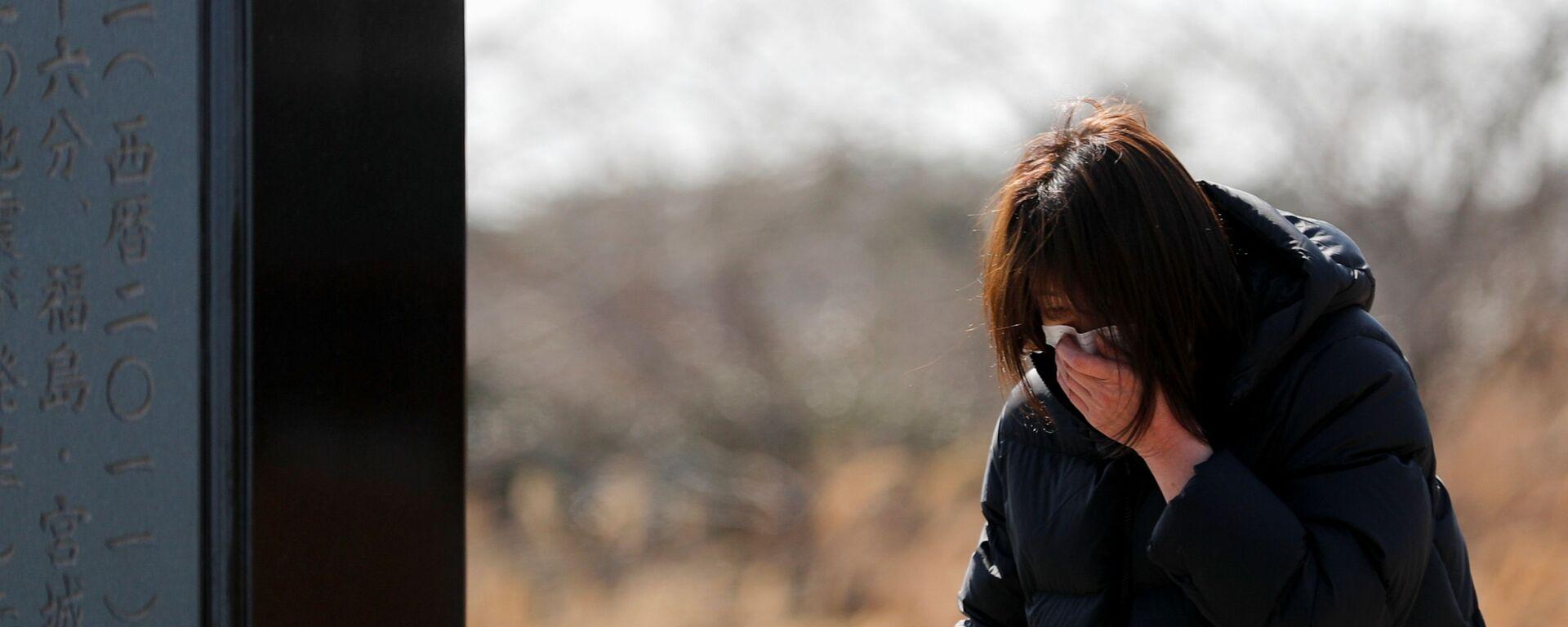 Девушка во время возложения цветов к памятнику жертвам землетрясения 2011 года в Японии  - Sputnik Таджикистан, 1920, 11.03.2021
