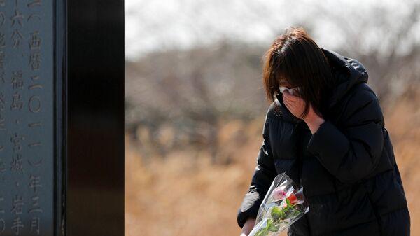 Девушка во время возложения цветов к памятнику жертвам землетрясения 2011 года в Японии  - Sputnik Таджикистан